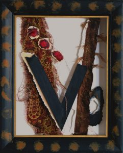 """Arranged blackpaper and paisley fabric in a """"V"""" design. Collage in a shadow box under glass by Leonard Gerwick"""
